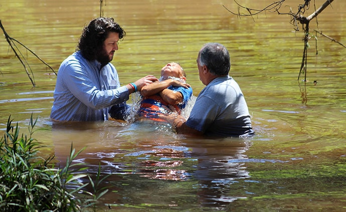 The Rev. Jarrod Caltrider (left) is a young United Methodist elder who serves three West Virginia churches, and he sometimes does creek baptisms. A new study of clergy age trends in the denomination shows the number of U.S. elders under age 35 is near a historic low. Photo courtesy of Jarrod Caltrider.