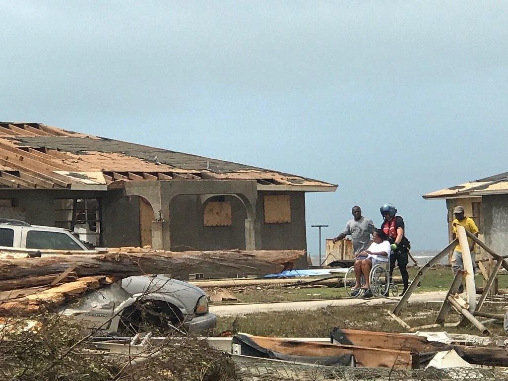 Um membro da tripulação do helicóptero da Guarda Costeira MH-60 Jayhawk, auxilia um grupo de pessoas que precisam de atenção médica nas Bahamas, em 4 de setembro. A Guarda Costeira está apoiando a Agência Nacional de Gerenciamento de Emergências das Bahamas e a Força de Defesa Real das Bahamas, que estão liderando os esforços de resposta, busca e salvamento nas Bahamas. Foto da Guarda Costeira dos EUA.