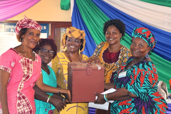 United Methodist Women regional missionaries Elmira Sellu (third from left) and Finda Quiwa (fourth from left) hold a lock box that is part of a new loan program for women during a four-day training in Freetown, Sierra Leone. The microfinance project, funded by United Methodist Women, is one of two empowerment programs the Regional Missionary initiative launched in September. Photo by Phileas Jusu, UM News.