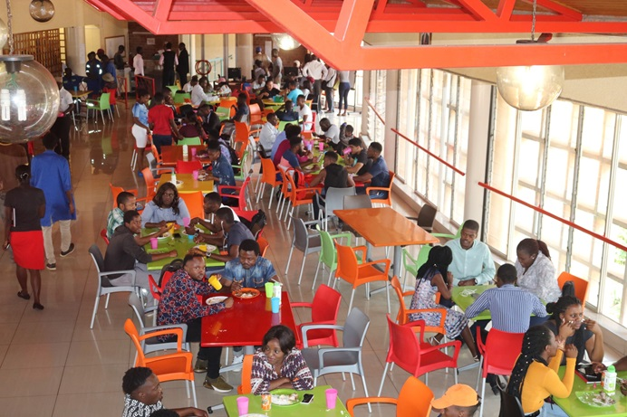Students eat in the cafeteria at Africa University, which serves about 1,200 people during lunch and dinner. To manage during tough economic times, the food services department has been stocking up on food and managing portions. Photo by Eveline Chikwanah, UM News.