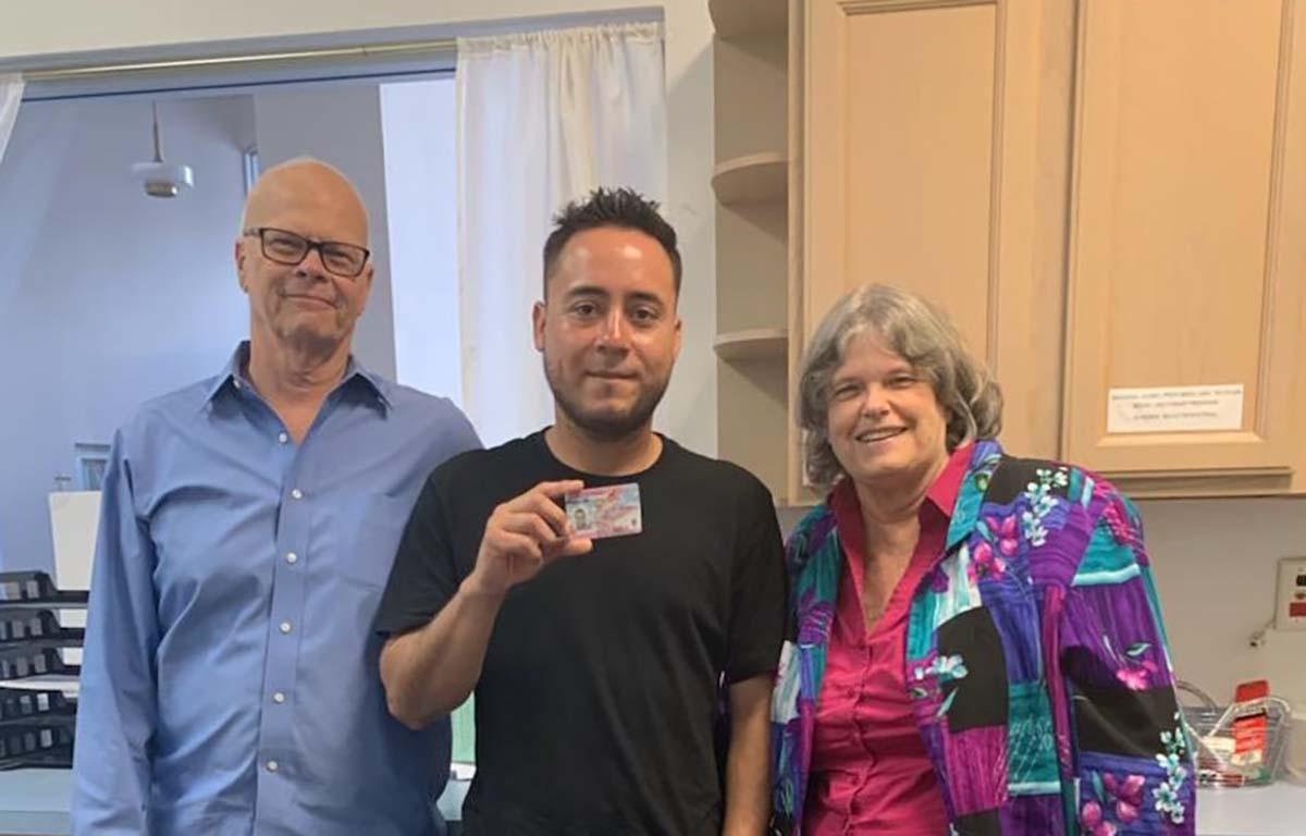 Os advogados da JFON da Flórida, Janet Horman e Roland Robinson, são fotografados com um cliente que recebeu seu documento de autorização de emprego. Foto cedida por Janet Horman.