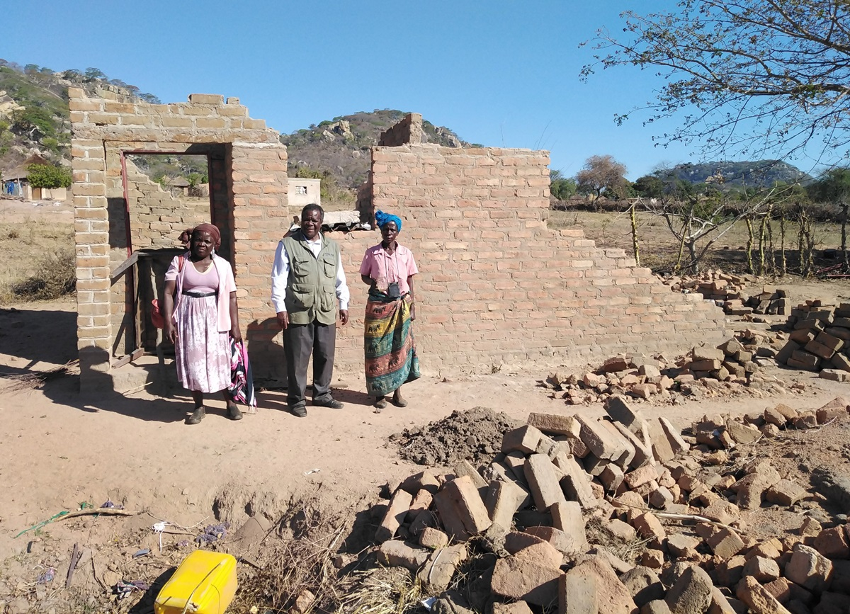 Vivian Chigweshe, right, stands in front of her home, which was destroyed by Cyclone Idai in March. She is among the survivors who will have a new house built with support from The United Methodist Church. Standing from left are lay leader Chirobwe Kupeti and the Rev. Jairos Mafondokoto, Masvingo District superintendent.  Photo by Chenayi Kumuterera, UM News.