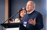 Bishop Michael McKee speaks during the United Methodist Council of Bishops meeting in Lake Junaluska, N.C., where the bishops learned that, at the current rate of giving, the bishops will run out of funds in 2024. McKee is president of the denomination's General Council on Finance and Administration. With him at the podium is Bishop Minerva Carcaño. Photo by Sam Hodges, UM News.