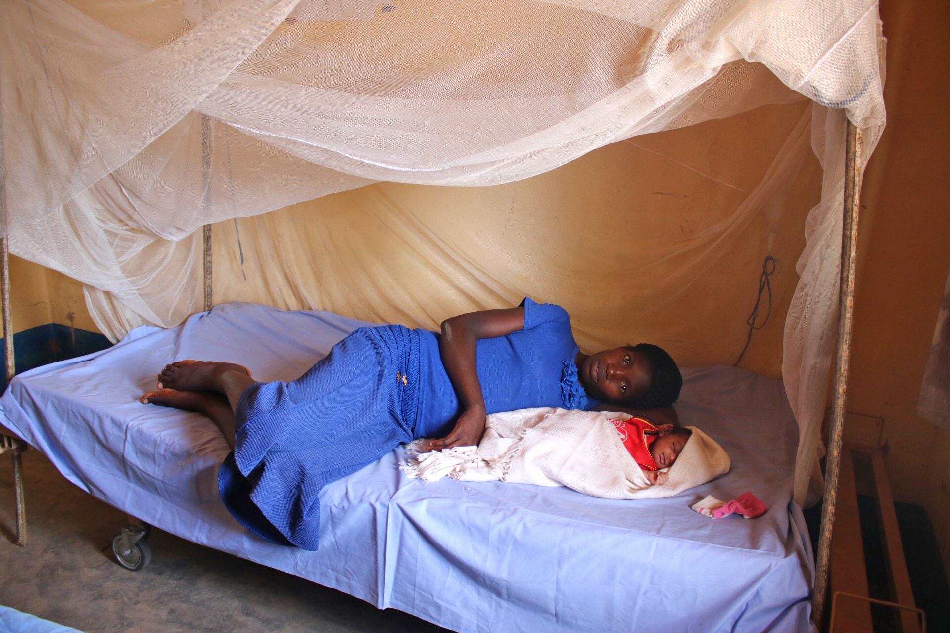 Madame Marie Kombe qui vient d'accoucher d'un petit garçon à la maternité Dingele se repose sur le lit avec son bébé. L'Eglise Méthodiste Unie a construit et équipé la maternité de Dingele dans le cadre du programme de santé globale dans la Conférence Annuelle du Congo Central. Photo de François Omanyondo Djonga, UMNS.