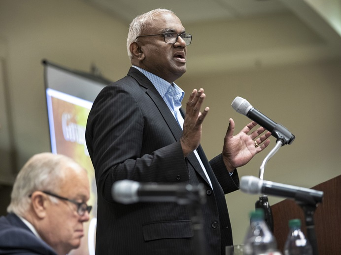 Moses Kumar, top executive of the General Council on Finance and Administration, addresses the Nov. 14-15 meeting of GCFA board of directors held in Nashville, Tenn. Seated is the North Texas Conference's Bishop Michael McKee, board president. Photo by Kathleen Barry, UM News.