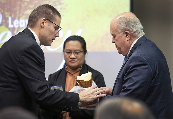 The Rev. Dustin Petz (left) of the Great Plains Conference hands bread to Bishop Michael McKee during the Nov. 15 communion service at the GCFA board meeting. Holding the chalice is board member Regan Reyes de Guzman of the Philippines. Photo by Kathleen Barry, UM News.
