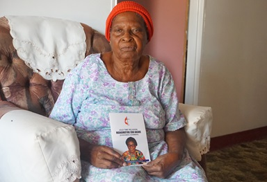 """Martha """"Granny"""" Mudzengerere shows off her new book, """"Old Time Religion,"""" which includes spiritual guidance and history about The United Methodist Church in Zimbabwe. It is the 104-year-old's first book. Photo by Kudzai Chingwe, UM News."""