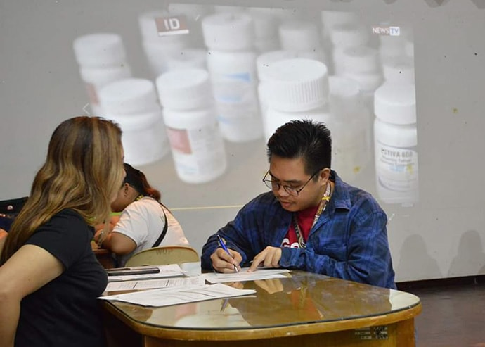 John Mark Santiago, former student governor of the College of Education local council at Wesleyan University-Philippines, signs paperwork to have his blood tested at an HIV and AIDS education and prevention forum at the university in Cabanatuan City, Philippines, on Oct. 30. Photo by Jon Balagan