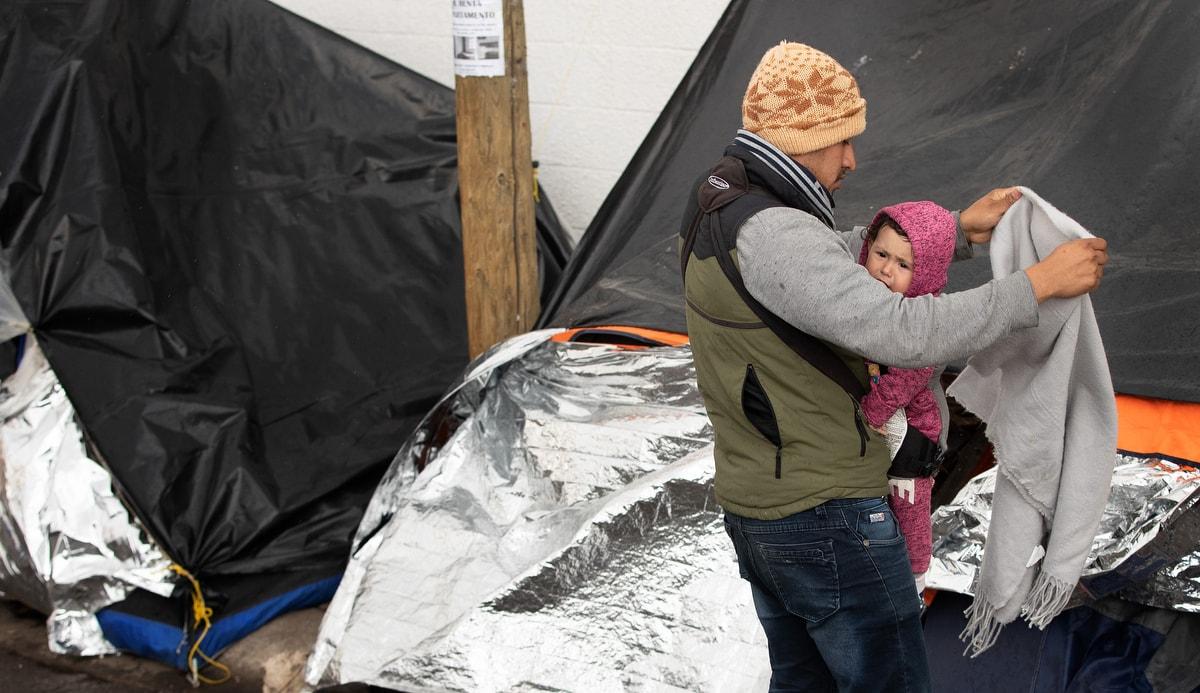 """Jesús, un migrante del estado de Michoacán en el oeste de México, trata de proteger a su hija de 1 año, Kataleya, de una llovizna fría que cae en el campamento donde viven al pie del puente internacional Paso del Norte en Juárez, México. Michoacán se encuentra entre los cinco estados de México considerados de mayor riesgo por parte del Departamento de Estado de los Estados Unidos, para los cuales ha emitido la advertencia de """"no viajar"""" a sus ciudadanos."""