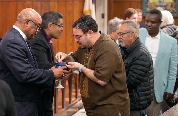 United Methodist Bishop W. Earl Bledsoe (left) and Bishop Felipe Ruiz Aguilar of the Methodist Church of Mexico serve Holy Communion during closing worship for the United Methodist Immigration Summit at Trinity-First United Methodist Church in El Paso, Texas. Photo by Mike DuBose, UM News.