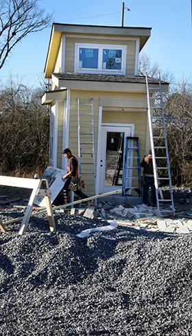 Carpenters work on details of one of the micro houses. Photo by Kathleen Barry, UM News.