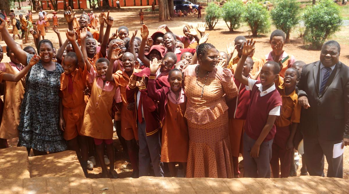 Elasto Musakanda (à droite), directeur de l'école primaire de Pagejo Rarubi, rit avec les élèves et le personnel de la ferme de Pagejo Rarubi dans la campagne zimbabwéenne. L'Eglise Méthodiste Unie établie sur la propriété paie les frais de scolarité de 20 élèves par an et fournit des fournitures et d'autres formes de soutien, a-t-il dit. Photo de Kudzai Chingwe, UM News.