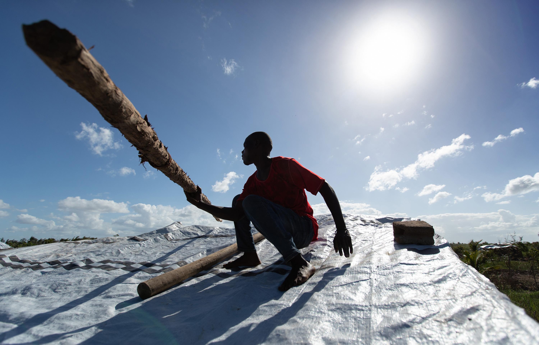 Jorge João Novo soulève un poteau en bois pour aider à fixer une bâche d'urgence sur sa maison après que le toit ait été arraché par le cyclone Idai à Buzi, au Mozambique. Photo de Mike DuBose, UM News.