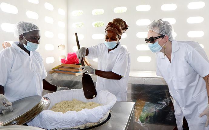 Lorrie King (à droite), directrice du développement durable à UMCOR, regarde Akossi Lobochi Rosine (à gauche) et Ayibé Carine fabriquer de l'attiéké dans une nouvelle usine de transformation à Anyama, en Côte d'Ivoire. L'attiéké est un plat ivoirien fabriqué à partir de farine de manioc dont la texture est similaire à celle du couscous. Photo de Isaac Broune, UM News.