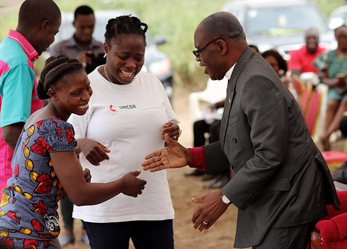Benjamin Boni, évêque de la région épiscopale de Côte d'Ivoire (à droite), félicite Angèle Seri, vice-présidente de Femmes Méthodistes Unies d'Issia, lors de l'inauguration, le 11 janvier, d'une usine de transformation d'attiéké à Anyama, en Côte d'Ivoire. Au centre se trouve Gisèle Koké, coordinatrice de projet du Réservoir de Siloé, l'organisation Méthodiste Unie qui a construit l'usine. Photo de Isaac Broune, UM News.