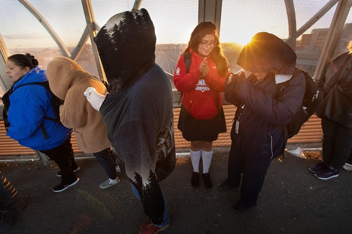 Ruth Moreno shows her brother, Lino, how to keep his hands warm as the sun rises behind them on the Santa Fe Bridge over the Rio Grande in Juárez, Mexico. They make the two-hour cross-border journey each school day to attend the United Methodist Lydia Patterson Institute in El Paso, Texas. Photo by Mike DuBose, UM News.