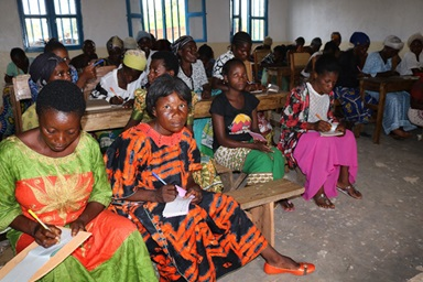 Helene Bataku (in orange dress), a member of Mwambangu United Methodist Church in Fizi, has learned to read and write at a new vocational center led by The United Methodist Church in Fizi, Congo. She said the center offers women new opportunities and a chance to catch up to their peers. Photo by Philippe Kituka Lolonga, UM News.
