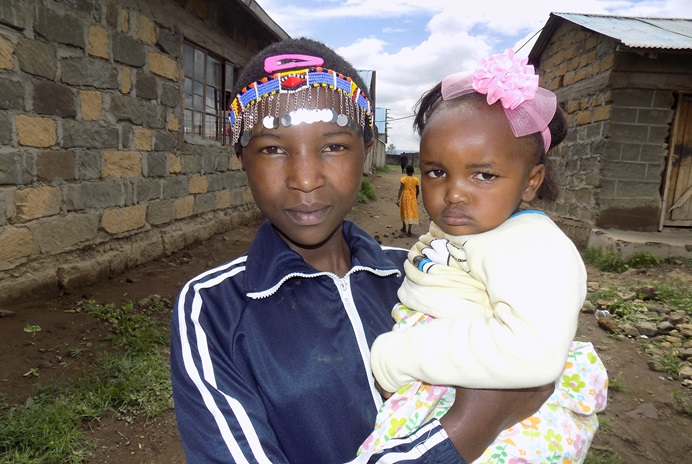 Jecinta Nairesea, 12, holds her 2-year-old daughter, Dorcus Nchorira, outside Trinity United Methodist Church in Gilgil, Kenya. The young mother was among those who attended the church's youth camp in December. Jecinta, who was forced to marry at age 9, now attends Trinity Mission Girls High School. Photo by Faith Wanjiru, UM News.