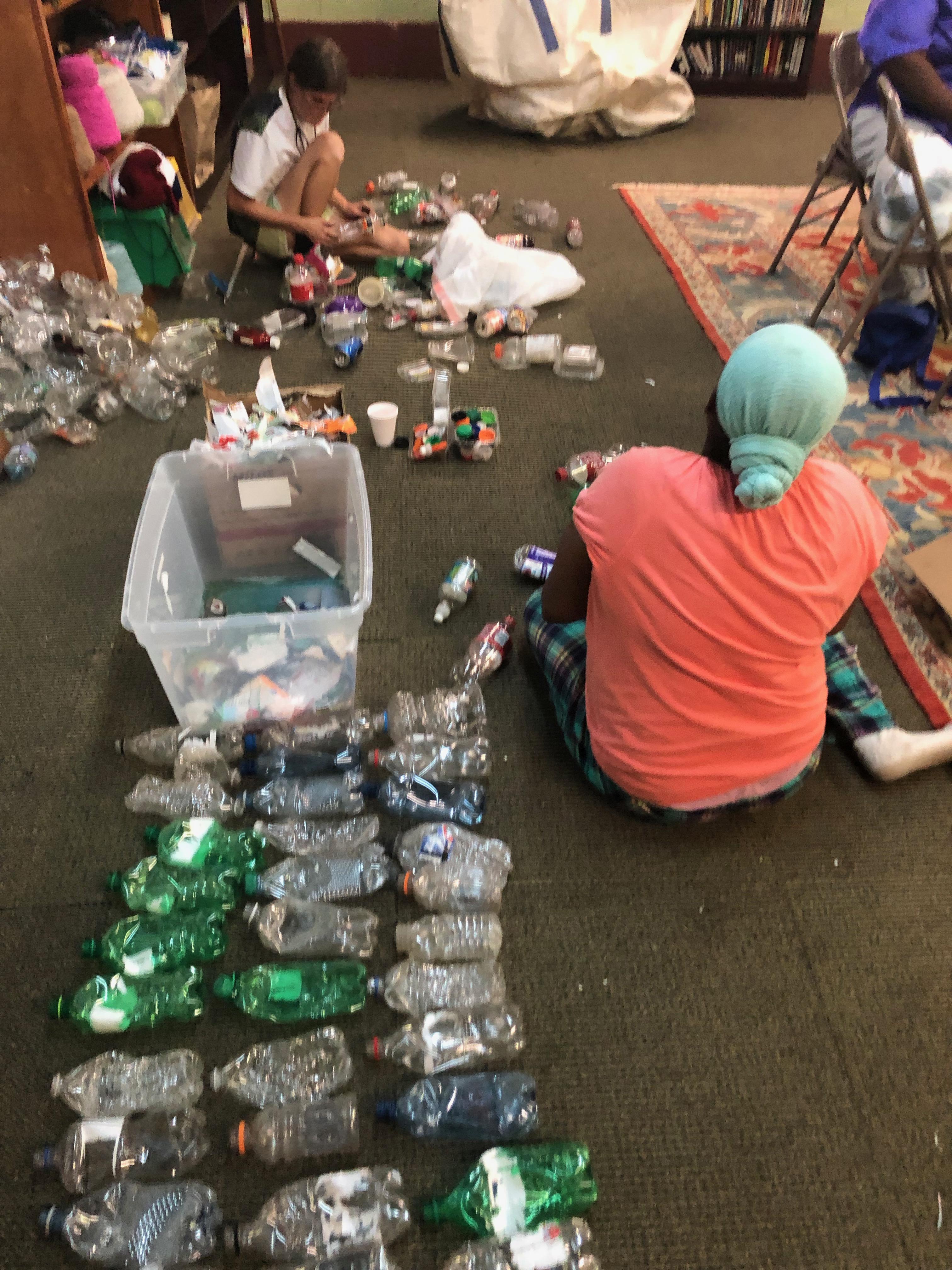 De izquierda a derecha están Amber Harrison y Celeste Vanhoose, quienes quitan las etiquetas y comprimen botellas de plástico para triturarlas. Foto de Mollie Erickson