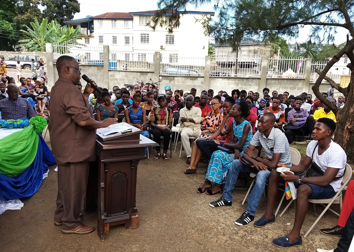Professor George Carew addresses students during orientation at the United Methodist University Preparatory Program campus in Brookfields, Sierra Leone, in western Freetown. The new program prepares students to retake their high school exit exams. Over 95% of Sierra Leonean students who took the 2019 West African Senior School Certificate Examinations failed to score high enough to meet university requirements. Photo by Phileas Jusu, UM News.