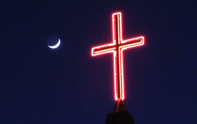 A neon cross atop Celebration United Methodist Church illuminates the night sky in Brandon, South Dakota. The pastor of the church, the Rev. Jason Martens, says the importance of frequent and frank communication can't be overstated in a church restart. Photo courtesy of the Rev. Jason Martens, Celebration United Methodist Church.