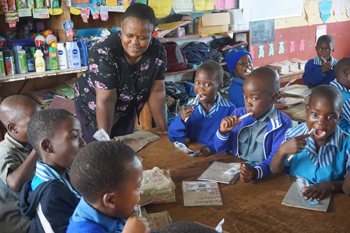 Nester Jeyacheya, deputy head of Mutambara Central Primary School, monitors children as they practice brushing their teeth at the United Methodist mission school in Chimanimani, Zimbabwe. The children learned proper brushing techniques and received toothbrushes and toothpaste as part of dental outreach program led by the church and a Swedish team with Dentists Without Borders. Photo by Kudzai Chingwe, UM News.