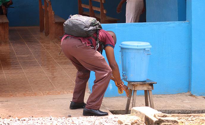 Un visiteur de l'hôpital Méthodiste Uni Mercy de Bo, en Sierra Leone, se lave les mains dans une station de lavage avant d'entrer dans l'hôpital le 16 mars. En raison des préoccupations liées aux coronavirus, l'utilisation de stations de lavage des mains, utilisées auparavant dans le cadre de la lutte contre le virus Ebola, a été renforcée dans les lieux publics, notamment les hôpitaux, les banques et les écoles. Photo de Phileas Jusu, UM News.
