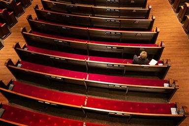 """Susan Logan worships in an empty pew section at Belmont United Methodist Church in Nashville, Tenn., Sunday, March 15, 2020, after church leadership encouraged people to worship from home via video livestream in response to the coronavirus. In keeping with the Metropolitan Nashville mayor's """"Safer at Home"""" directive, the church building has since been closed. Photo by Mike DuBose, UM News."""