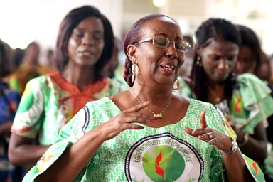 Lydie Acquah (front) joins in singing during the 10th anniversary celebration for the Voice of Hope (La Voix de l'Espérance), the radio station of The United Methodist Church in Côte d'Ivoire, at Jubilee United Methodist Church in Abidjan. Acquah is the station's director. Photo by Isaac Broune, UM News.