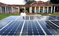 Dr. Joseph Kayembe Katongola stands in front of United Methodist Kabongo Hospital's new solar panel station. Doctors at the hospital in Kabongo, Congo, had been operating by candlelight before the system was installed earlier this year. Photo by Faustin Kabila Mande.